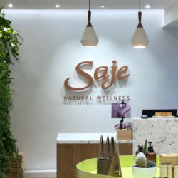 Image of the Saje Natural Wellness Interior, showing the Saje logo on the wall behind the check out counter.