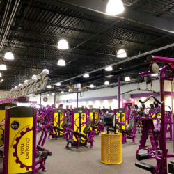Image of a Planet Fitness interior, showing a large room filled with exercise and strength training equipment.