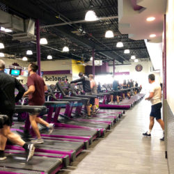 Image of a Planet Fitness interior, showing patrons jogging on treadmills.